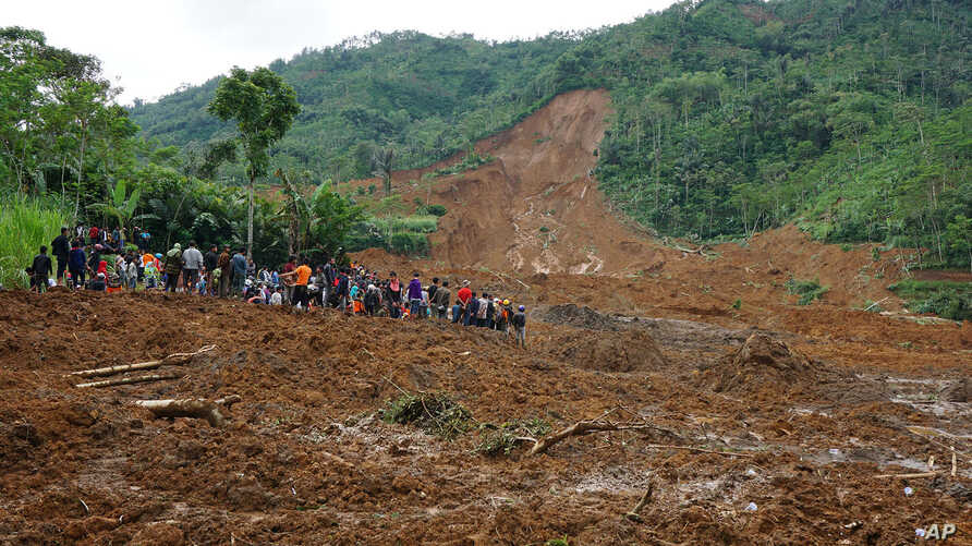 Villagers and rescuers examine the site where a landslide swept away houses in Jemblung village, Central Java, Indonesia, Dec. 13, 2014.