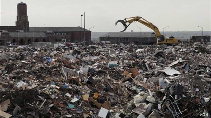 A piece of construction equipment works on the pile of debris, collected during the cleanup from Superstorm Sandy, in the parking lot of Jacob Riis Park in the Rockaway section of the Queens borough of New York, November 14, 2012.