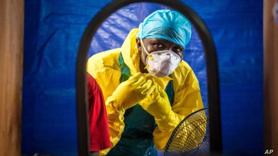 In this Thursday, Oct. 16, 2014 file photo, a healthcare worker dons in protective gear before entering an Ebola treatment center in the west of Freetown, Sierra Leone. (AP Photo/Michael Duff, File)
