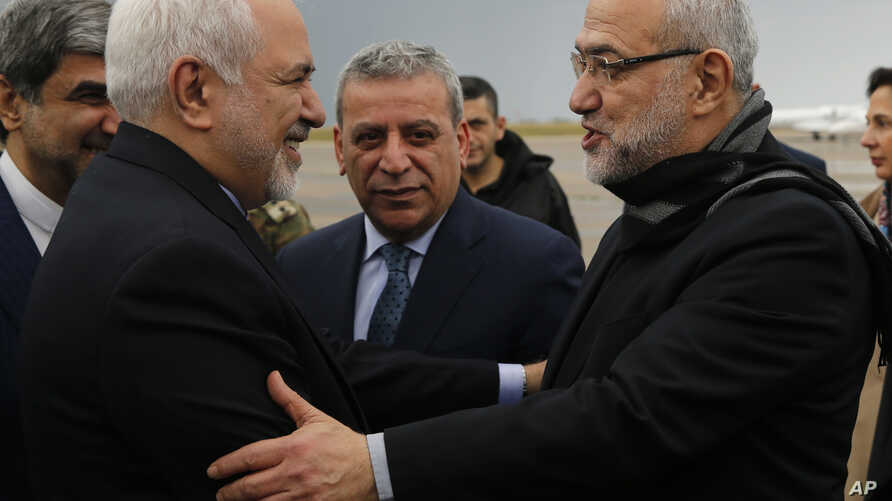 Iran's Foreign Minister Mohammad Javad Zarif, left, is greeted by Lebanese Minister of State Parliamentary Affairs and a member of Hezbollah politicians block Mahmoud Qmati, on his arrival at Rafik Hariri Airport, in Beirut, Feb. 10, 2019.