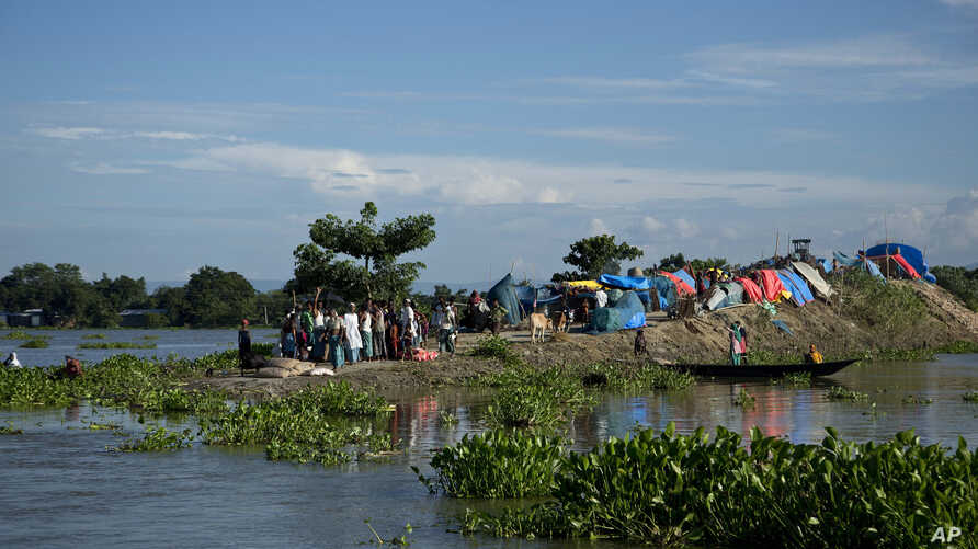 FILE- In this July 31, 2016, file photo, flood affected villagers take shelter on the elevated portion of a submerged road in Morigaon district, east of Gauhati, northeastern Assam state, India.