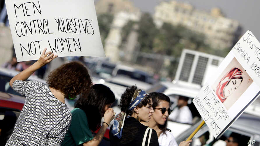FILE - Egyptian women hold banners during a protest against sexual harassment in Cairo, Egypt, June 14, 2014.