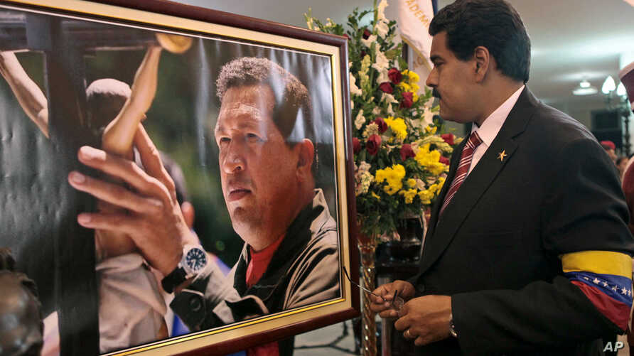 Venezuela's acting President Nicolas Maduro stands in front of a portrait of Venezuela's late President Hugo Chavez after a symbolic swearing in ceremony, March 8, 2013.
