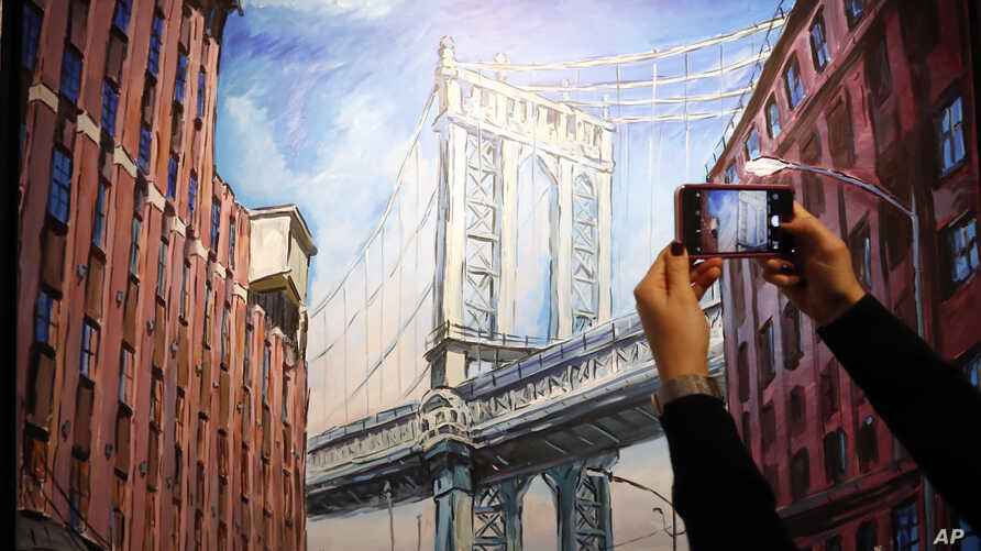 """A woman takes a picture of a painting by Bob Dylan called """"Manhattan Bridge, Downtown New York"""" on display at the exhibition called Bob Dylan The Beaten Path, at the Halcyon Gallery in London, Tuesday, November. 1, 2016. The exhibition opens on Novem"""