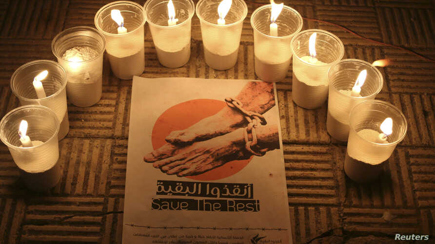 FILE - Lit candles are placed by activists around a placard during a vigil in solidarity with the detainees in Syrian prisons at Aleppo's Salaheddine neighborhood, Jan. 26, 2015.