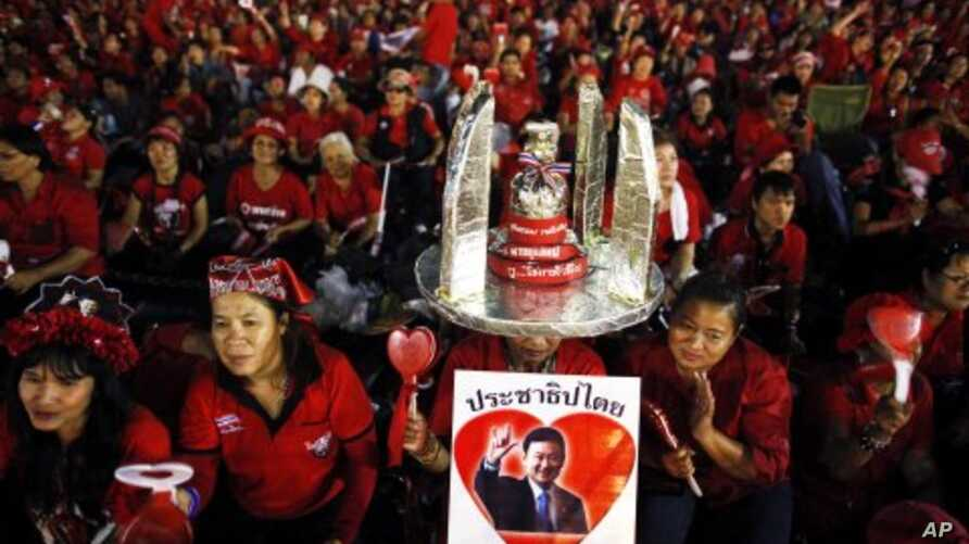 Anti-government ''red shirt'' protesters hold a picture of former Thai premier Thaksin Shinawatra as they wait for him to address them over a link during a rally near the Democracy monument, the site of bloody clashes with security forces last year,