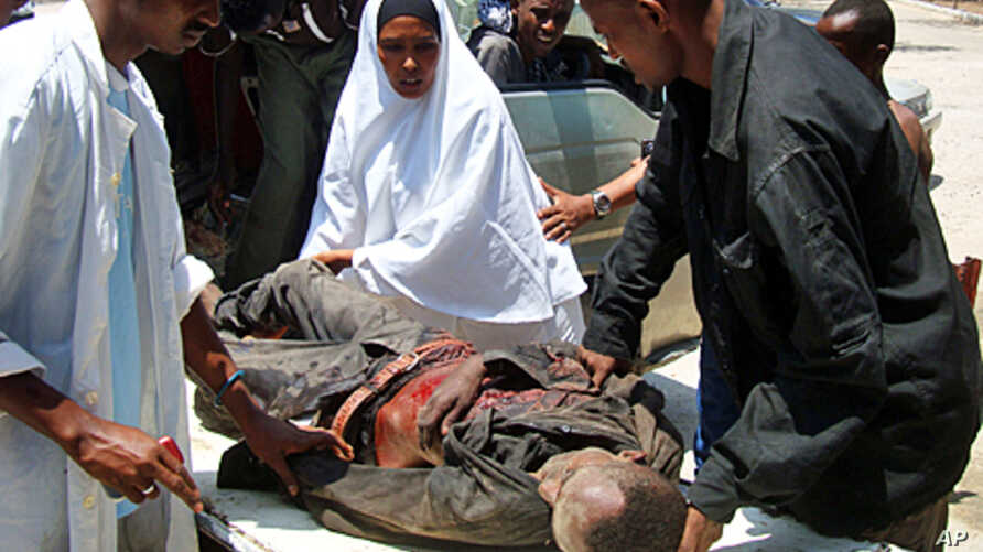 Residents assist a civilian wounded in a crossfire during fighting between government soldiers and Islamist rebels in Hodan district, northern Mogadishu, March 13, 2011