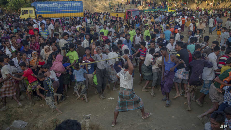 A Rohingya Muslim, who crossed over from Myanmar into Bangladesh, beats other refugees as a fight broke out during a distribution of aid near Balukhali refugee camp, Bangladesh, Sept. 25, 2017.