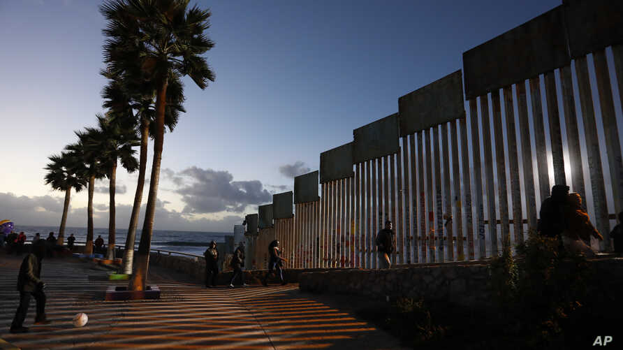 People walk along the U.S. border wall in an oceanside park in Tijuana, Mexico, at sunset, Nov. 30, 2018.