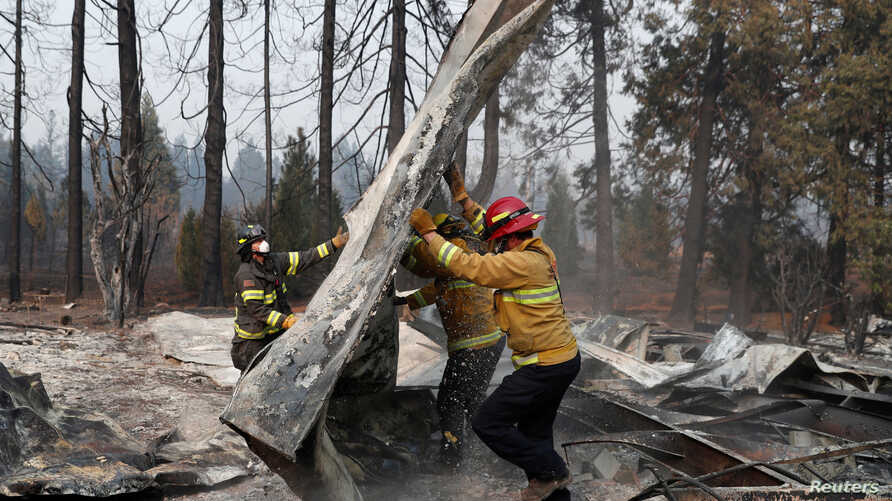 Firefighters move debris while recovering human remains from a trailer home destroyed by the Camp Fire in Paradise, California, U.S., Nov. 17, 2018.