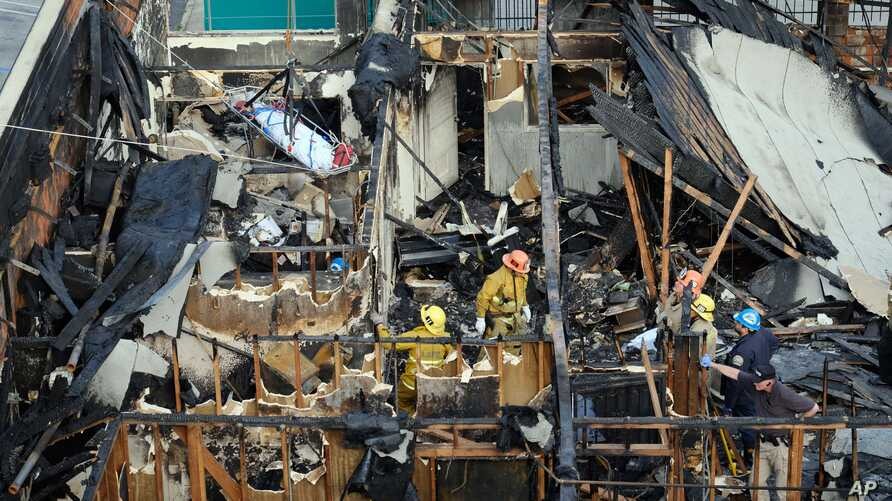 A ladder truck lifts a body, one of four additional bodies found in the burned-out ruins of an abandoned office building in the Westlake district just west of downtown Los Angeles Tuesday, June 14, 2016.