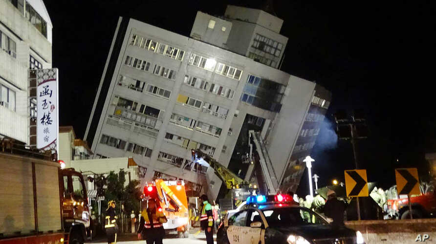 Rescuers are seen entering a building that collapsed onto its side from an early morning 6.4 magnitude earthquake in Hualien County, eastern Taiwan, Wednesday, Feb. 7 2018.  Rescue workers are searching for any survivors trapped inside the building. ...
