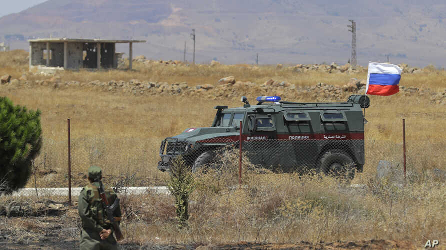 Syrian army soldier stands guard as Russian military police vehicle passes by near the town of Alhureyeh, Aug. 14, 2018.