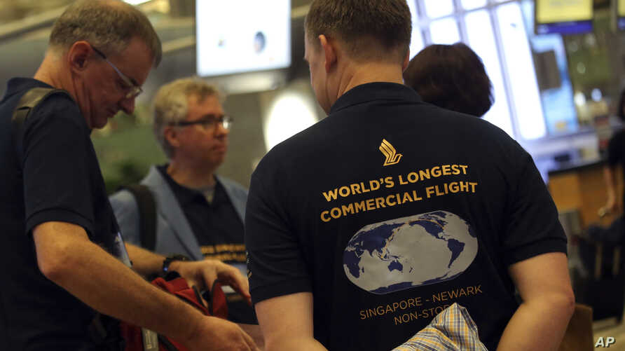 Passengers wearing self-designed T-shirts which celebrate their trip on Singapore Airline's inaugural non-stop flight to New York, wait at the check-in counter in Singapore, Oct. 11, 2018.