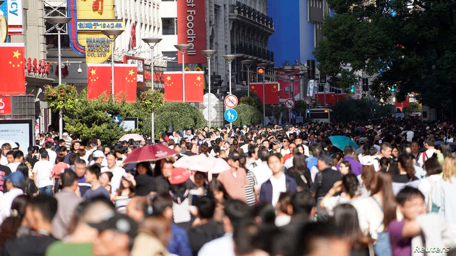 Chinese national flags are seen as tourists throng the Nanjing pedestrian road, a main shopping area, on China's 69th National Day in Shanghai, China, Oct. 1, 2018.