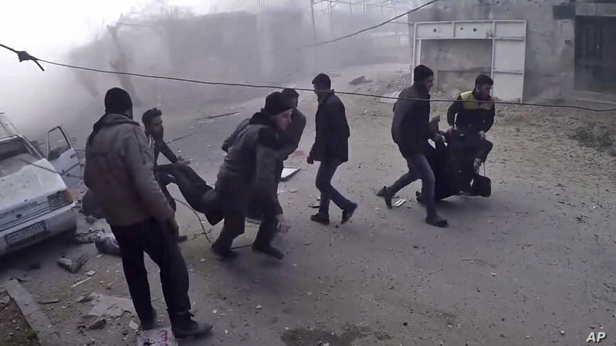 This frame grab from video released by the Syrian Civil Defense White Helmets, which has been authenticated based on its contents and other AP reporting, shows members of the Syrian Civil Defense group and civilians carrying victims after airstrikes