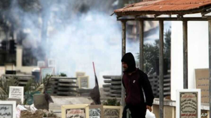 An anti-government protester carrying water to throw on tear gas canisters fired by riot police, moves through a cemetery as gas billows behind him in the Shiite Muslim village of Jidhafs, Bahrain, on the outskirts of the capital of Manama, March 17,