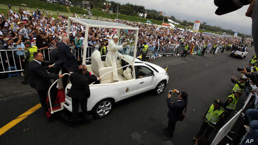 Pope Francis waves from his popemobile as he arrives to offer a giant outdoor mass in Medellin, Colombia, Sept. 9, 2017.