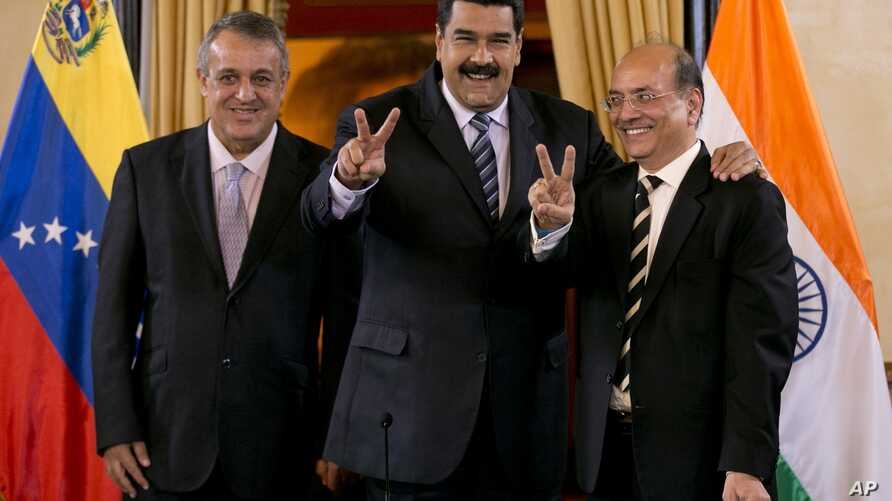 Venezuela's President Nicolas Maduro, center, and Executive Director of Oil and Natural Gas Corporation, Narendra Kumar Verma, flash victory hand signs as they pose for a photo in Caracas, Venezuela, Nov. 4, 2016.  At right is PDVSA President Eulogio