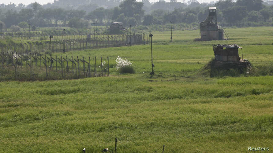 Indian security posts, right, are seen along the border between India and Pakistan in Suchetgarh near Jammu, Oct. 9, 2014.