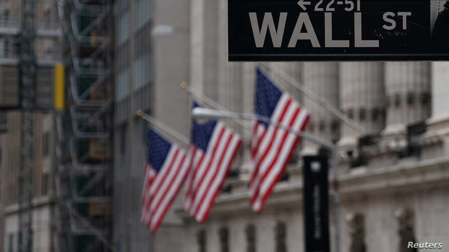 FILE - The Wall Street sign is pictured in front of the New York Stock Exchange in New York City.