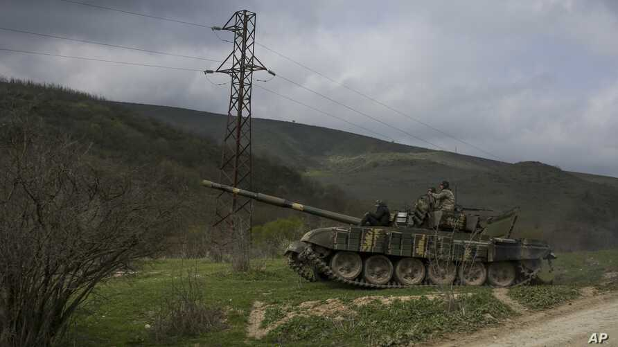 Armenian soldiers patrol on a tank near the village of Madaghis in Nagorno-Karabakh, Azerbaijan, April 6, 2016. Two Armenian soldiers were killed in fighting with Azerbaijani forces around Friday even though a cease-fire appears to be largely holding