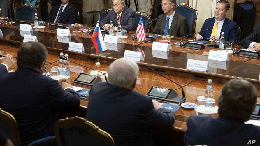 Top from left: a member of the Senate of the legislative Assembly of the state of Texas Peter Hettler, Texas Sen. Don Huffines, Sen. Rand Paul and his communications director Sergio Gor attend a meeting with Russian lawmakers in Moscow, Aug. 6, 2018.