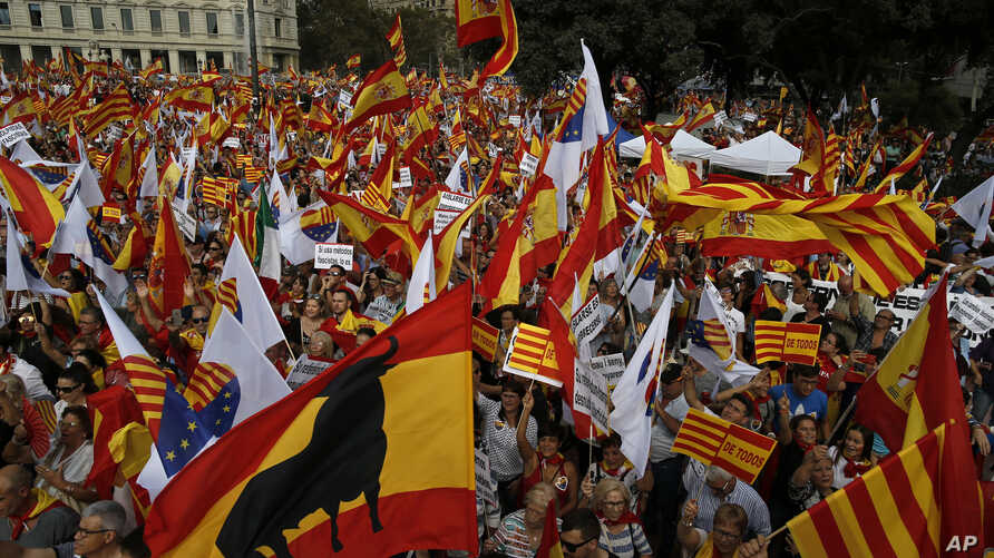 "People wave flags of Catalonia and Spain as they celebrate a holiday known as ""Dia de la Hispanidad"" or Spain's National Day in Barcelona, Spain, Oct. 12, 2017."