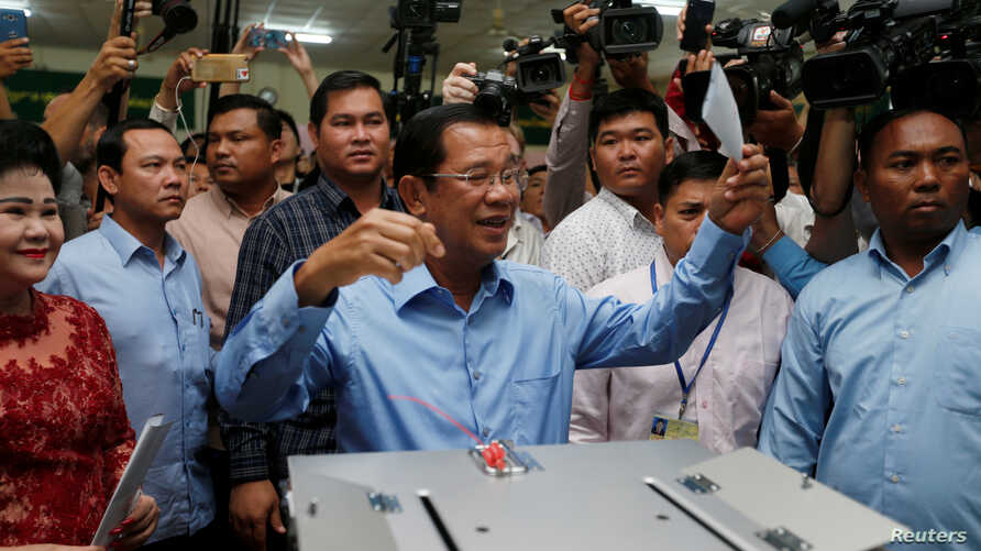 Cambodian Prime Minister Hun Sen prepares to cast his vote as his wife, Bun Rany, stands beside him at a polling station during a general election in Takhmao, Kandal province, Cambodia, July 29, 2018.