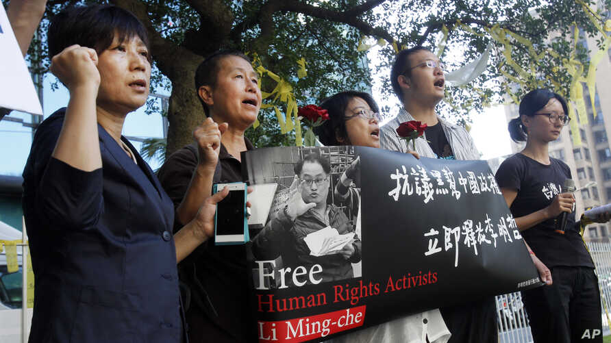 Supporters of Taiwanese activist Lee Ming-che detained in China, chant their support during a media event in Taipei, Taiwan, Nov. 28, 2017.
