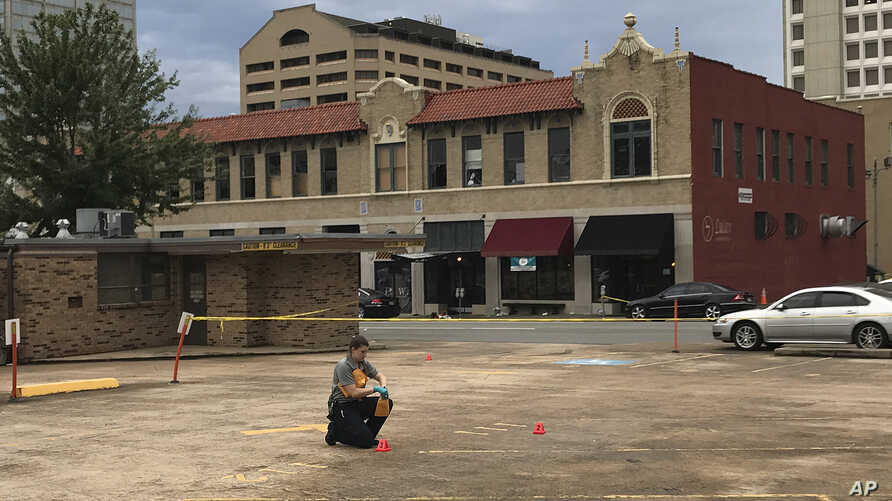An investigator collects evidence near an Arkansas nightclub where police say multiple people were shot, Saturday, July 1, 2017, in Little Rock, Ark.