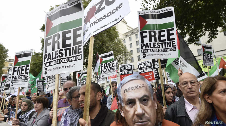 A demonstrator wears a Benjamin Netanyahu mask with a message written on it during a protest outside Downing Street in London, Britain Sept. 9, 2015.