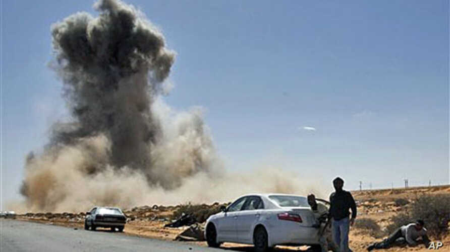 Smoke rises following an air strike by Libyan warplanes near a checkpoint close to the anti-Gadhafi rebels' checkpoint in the oil town of Ras Lanouf, eastern Libya, March 7, 2011