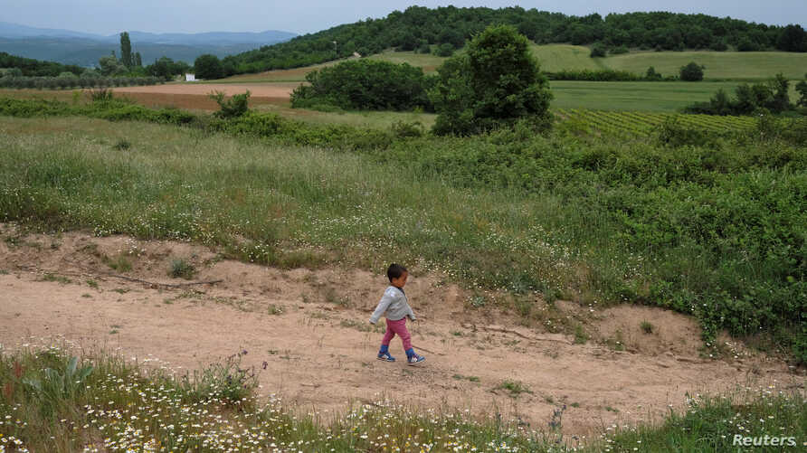 A child who tried to cross the border walks back to a makeshift camp for refugees and migrants at the Greek-Macedonian border near the village of Idomeni, Greece, May 11, 2016.
