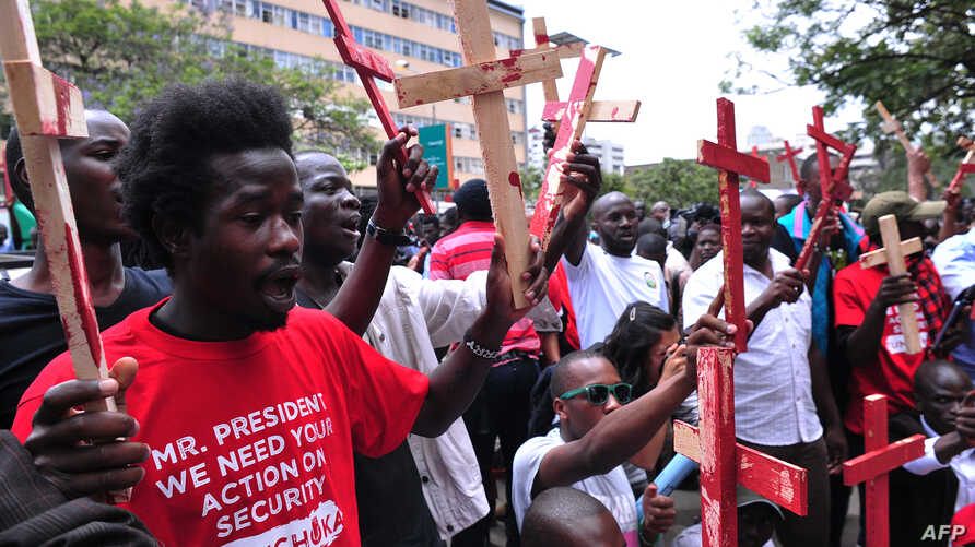 People hold wooden crosses  to represent those killed in a string of attacks, during a demonstration to demand greater security on Nov. 25, 2014 in Nairobi.
