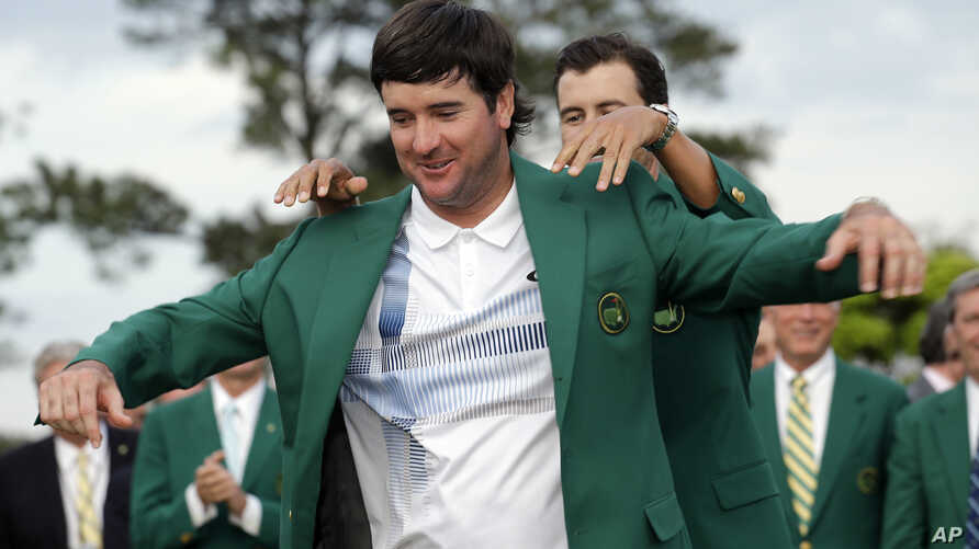 Defending Masters' champion Adam Scott, of Australia, helps Bubba Watson, left, with his green jacket after winning the Masters golf tournament Sunday, April 13, 2014.