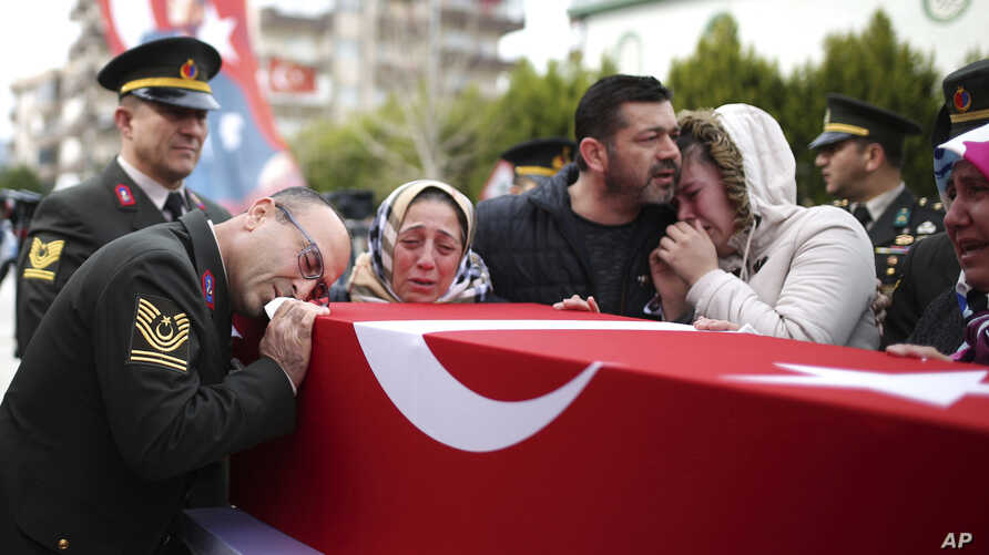 Family members mourn over the coffin of Ugur Palanci, 28, during a funeral ceremony in Izmir, Turkey, March 2, 2018. Taha Palanci was one of eight Turkish soldiers killed Thursday in fighting against Syrian Kurdish militia in Afrin, northwestern Syri