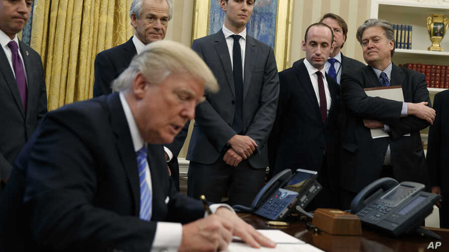 White House chief strategist Steve Bannon (far right) is among the top policy advisers present as President Donald Trump signs an executive order in the Oval Office, Monday, Jan. 23, 2017.