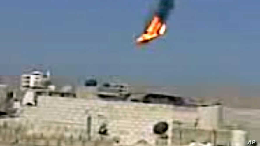 This citizen journalism image purports to show a Syrian military helicopter on fire and falling to the ground after it was apparently hit during fighting between government forces and rebels in Damascus, Aug 27, 2012. AP IS UNABLE TO INDEPENDENTLY VE