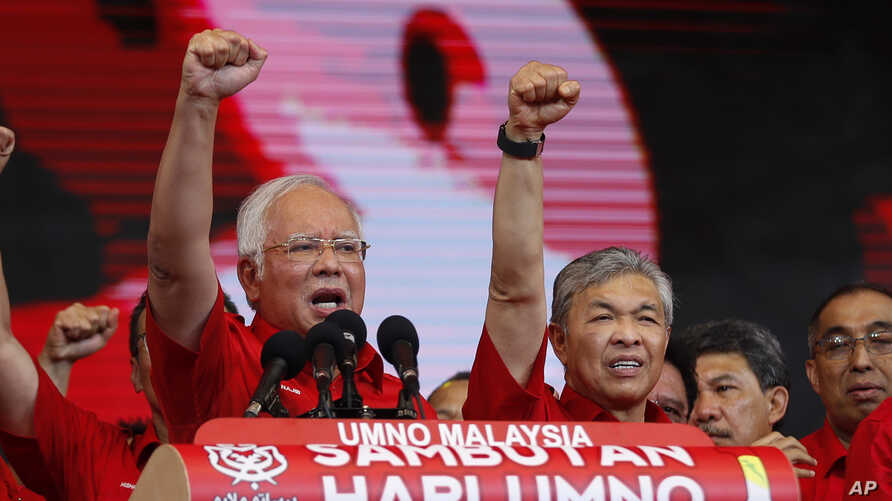 Malaysian Prime Minister and President of Malaysia's ruling party United Malays National Organization's (UMNO) Najib Razak (left) and Deputy Prime Minister Ahmad Zahid Hamidi chant a slogan during a celebration of party's 71st anniversary in Kuala Lu