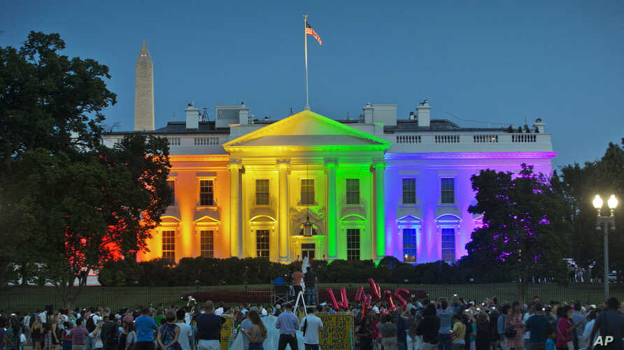People gather in Lafayette Park to see the White House illuminated with rainbow colors in commemoration of the Supreme Court's ruling to legalize same-sex marriage in Washington, June 26, 2015.