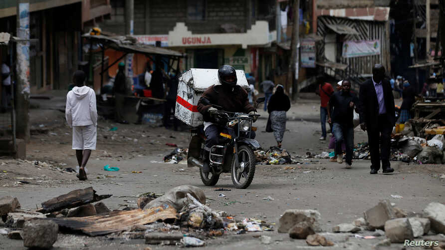 A motorcyclist drives through obstacles placed on a street by supporters of opposition leader Raila Odinga during the latest protests in Mathare, Nairobi, Kenya, August 14, 2017.