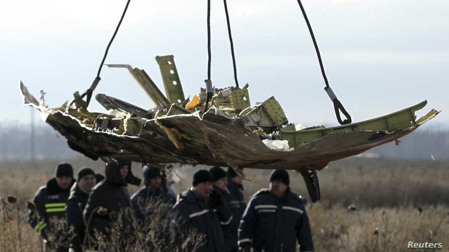 A crane transports a piece of the Malaysia Airlines flight MH17 wreckage at the crash site in eastern Ukraine's Donetsk region, Nov. 20, 2014.