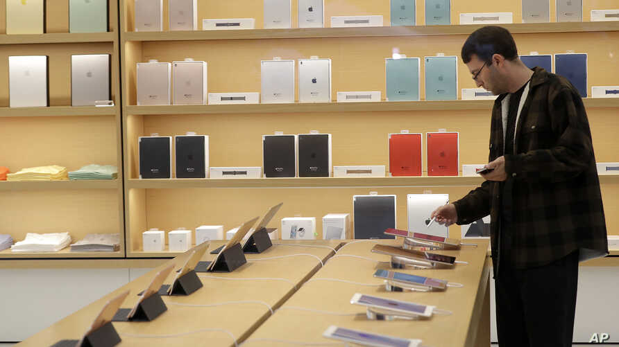 A shopper looks at iPad tablets displayed at a store on Apple's campus before an announcement of new products, Oct. 27, 2016, in Cupertino, Calif.