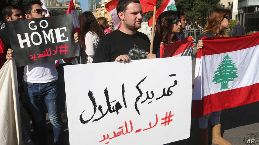 "FILE - Activists hold Lebanese flags and an Arabic placard, center, that reads:""your extension is an occupation, no to the extension,"" during a protest against the extension of the Lebanese parliament, on a road that leads to the Parliament building,"