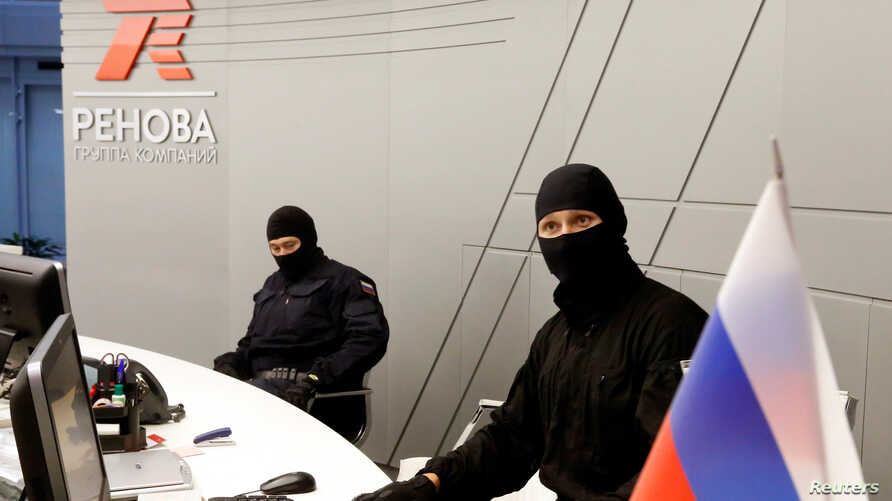 FILE - Members of Russia's FSB security service are seen during a search of the offices of T Plus, a subsidiary of Renova in Moscow, Russia, Sept.  5, 2016.