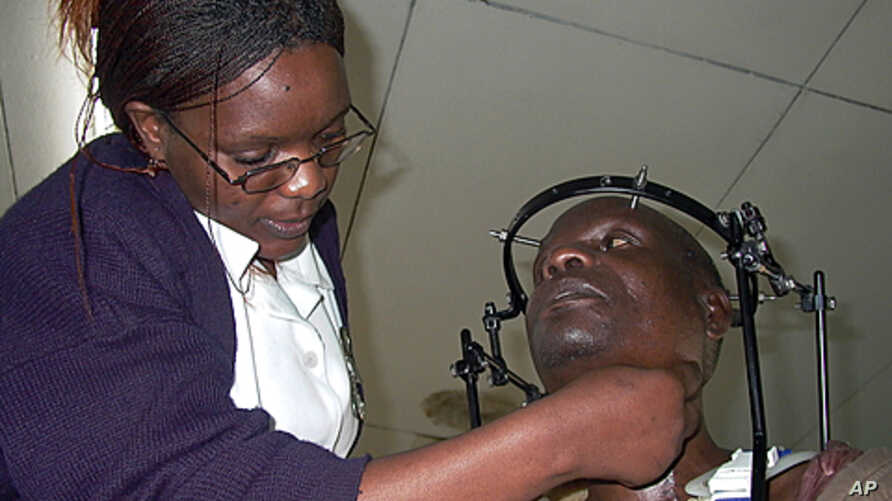 A nurse examines a patient suffering from Tuberculosis TB of the bones, cramped with metals to keep his bones tight, at Queen Elizabeth Central Hospital in Blantyre. (file photo)