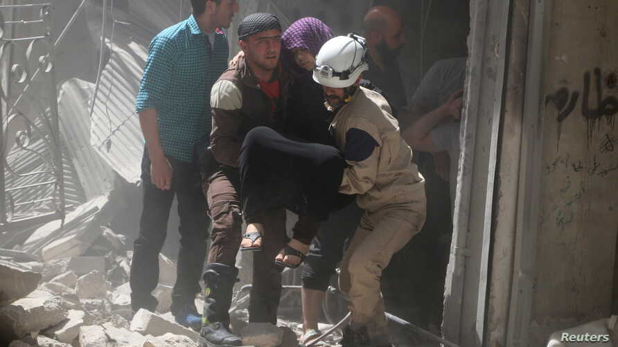 Civil defense members evacuate a woman from a damaged building after airstrikes in the rebel held area of old Aleppo, Syria, April 22, 2016.