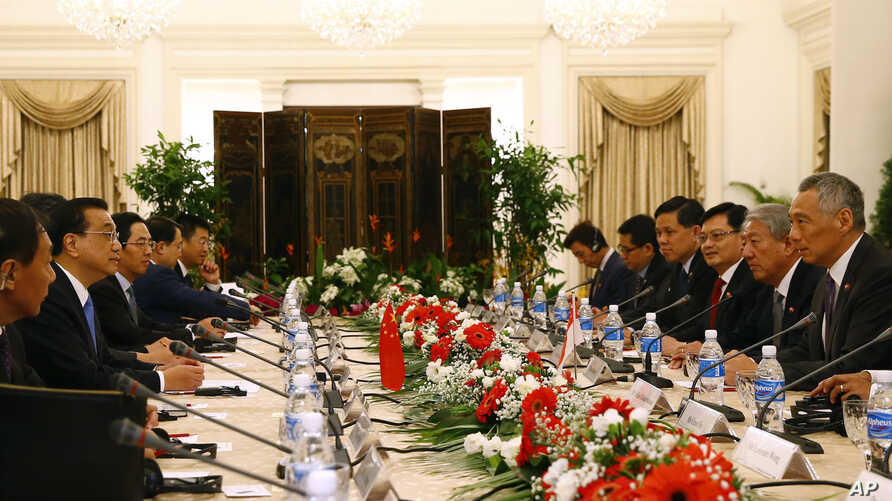 China's Premier Li Keqiang, second left, and Singapore's Prime Minister Lee Hsien Loong, right, attend a meeting with their respective delegations at the Istana or presidential building in Singapore, Nov. 12, 2018.