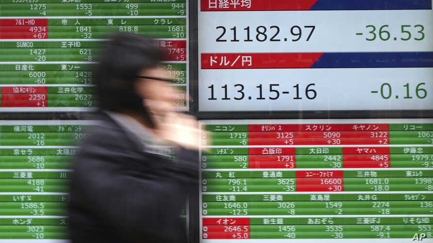A man walks past an electronic stock board showing Japan's Nikkei 225 index at a securities firm in Tokyo, Dec. 11, 2018.